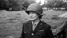 Lee Miller: A Woman's War - Lee Miller in steel helmet specially designed for using a camera, Normandy, Unknown Photographer, 1944. (c) Lee Miller Archives